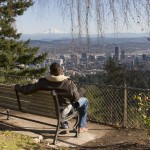 Man at bench overlooking portland oregon